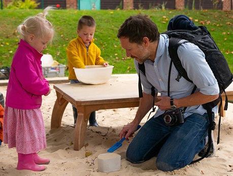 Photographer Danny Burrows with children in sandpit